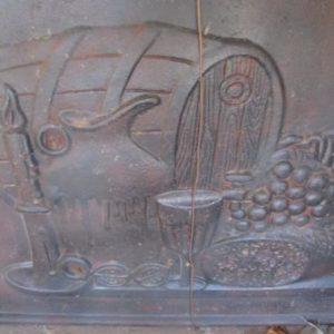 Piastra in ghisa per camino raffigurante pane, uva, barile, giara e un lume con condela. Ra- materiale antico e di recupero