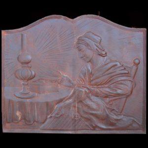 Piastra in ghisa per camino raffigurante donna che cuce al lume di una lampada.